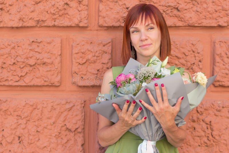 Stående av en flicka med en stilfull bukett på väggbakgrunden arkivbild