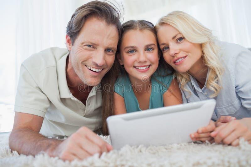Stående av en flicka och henne föräldrar som använder en minnestavla arkivbild