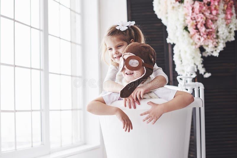 Stående av en flicka och en pojke i den pilot- hatten som spelar i badrum på piloter eller sjömän Begreppet av loppet, barndom oc royaltyfria foton