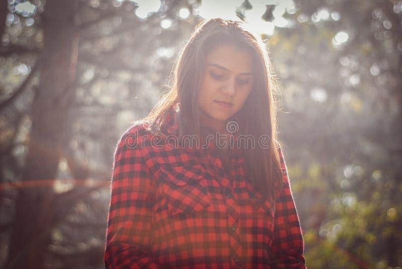 stående av en flicka på en varm höstskogbakgrund suddighet bakgrund Bokeh verkställer royaltyfria bilder