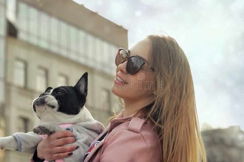 Stående av en flicka som rymmer hennes hund i henne armar royaltyfri fotografi