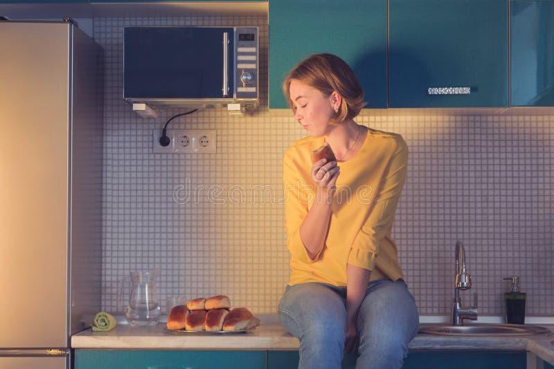 Stående av en flicka som ser med nöje på bakelserna som sitter på tabellen i köket royaltyfri fotografi