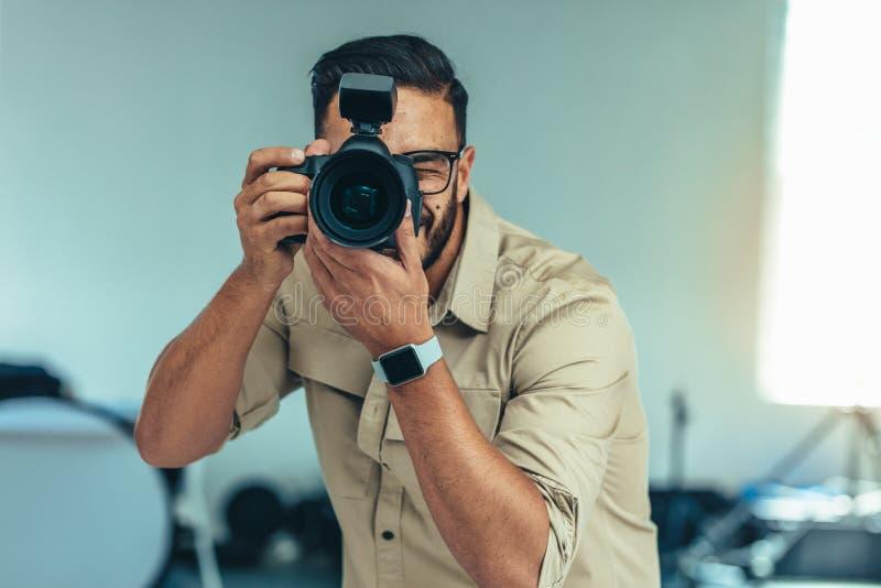 Stående av en fotograf som tar fotoanseende i en studio arkivbild