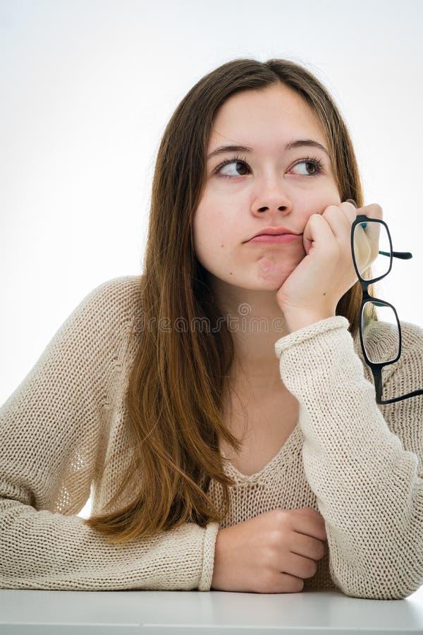 Stående av en fundersam tonårs- flicka på skrivbordet arkivfoton