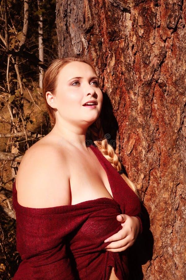 Stående av en fyllig ung kvinna med stora bröst royaltyfria foton