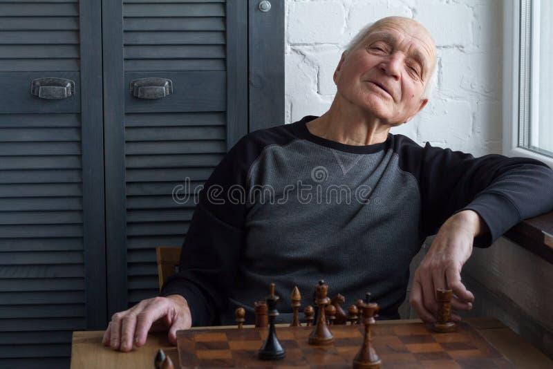 Stående av en gamal man, som ser rak in i kameran och leendena över den vita tegelstenväggen och det gråa kabinettet, selektiv fo royaltyfria bilder