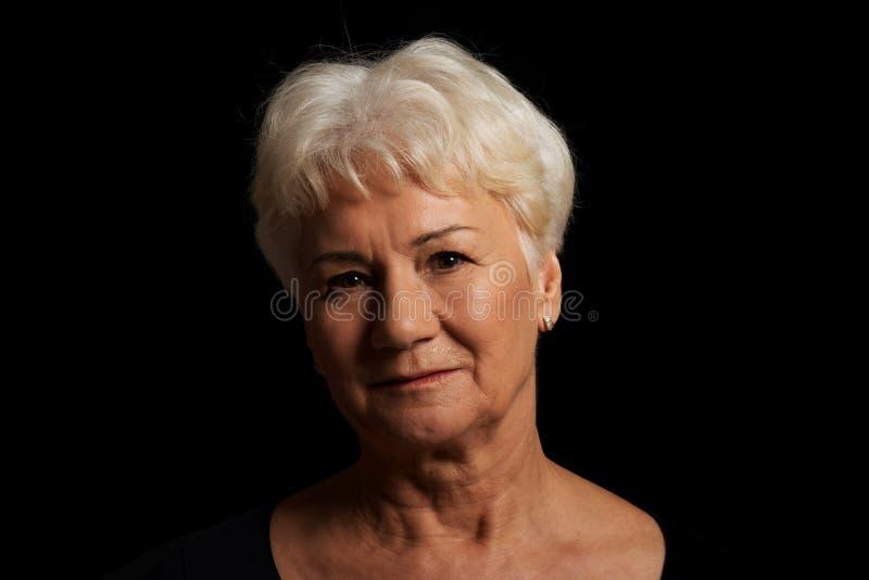 Stående av en gammal attraktiv dam över svart arkivbild