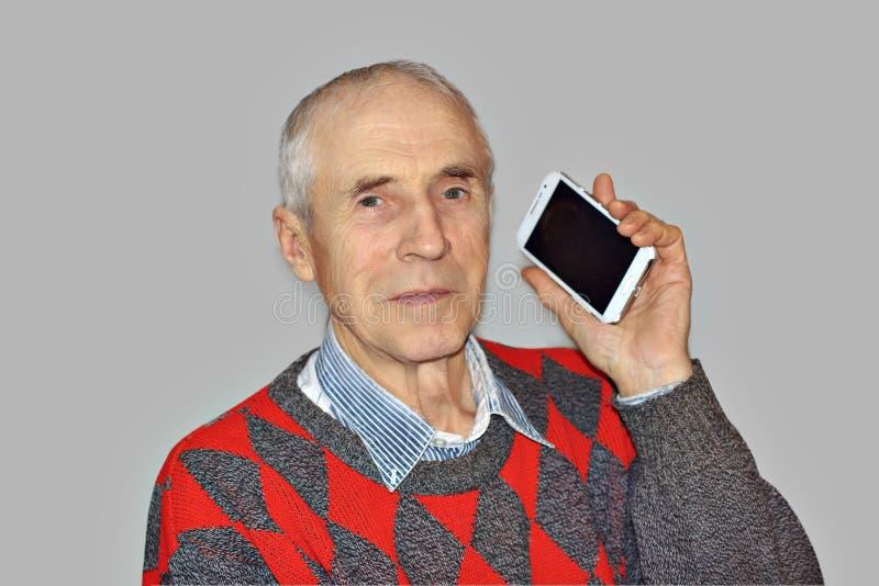 Stående av en gammal hög man med en telefon arkivbilder