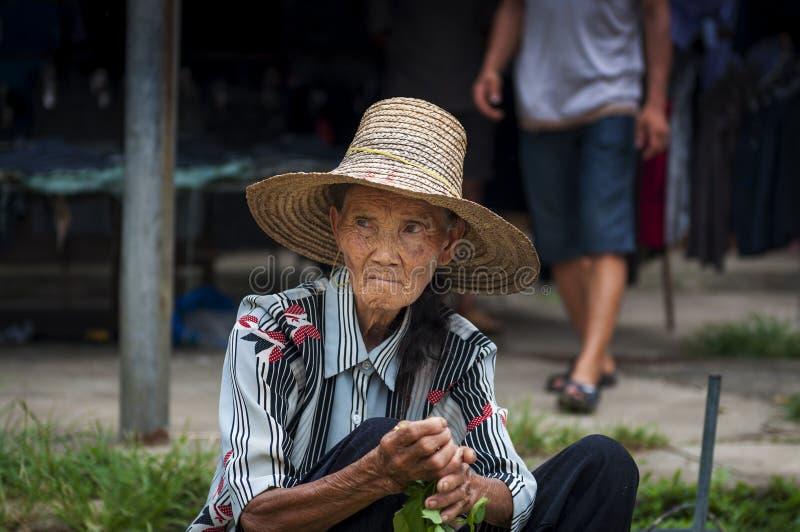 Stående av en gammal kinesisk kvinna som säljer grönsaker i en gatamarknad på den Fuli byn i bygden av sydliga Kina royaltyfria bilder