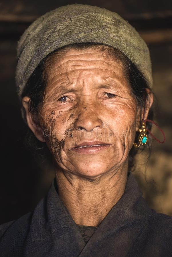 Stående av en gammal nepalese kvinna i medborgarekläder i henne hus royaltyfri fotografi