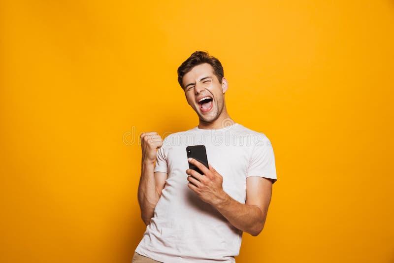 Stående av en glad hållande mobiltelefon för ung man royaltyfria foton