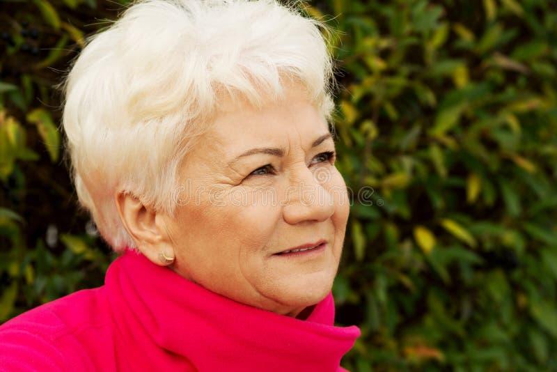 Stående av en gladlynt gammal dam över grön bakgrund. fotografering för bildbyråer