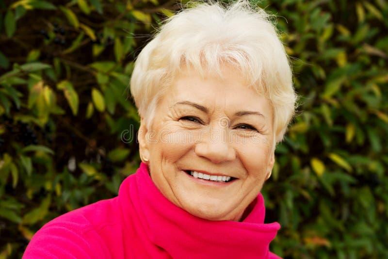 Stående av en gladlynt gammal dam över grön bakgrund. arkivbilder