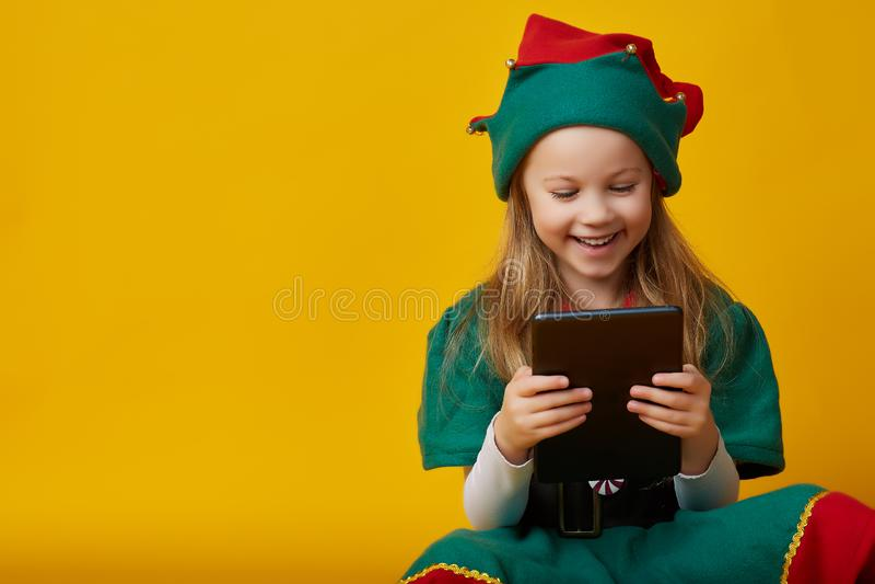 Stående av en gladlynt lycklig europeisk liten flicka i älvadräkt som skrattar rymma minnestavlan royaltyfria foton