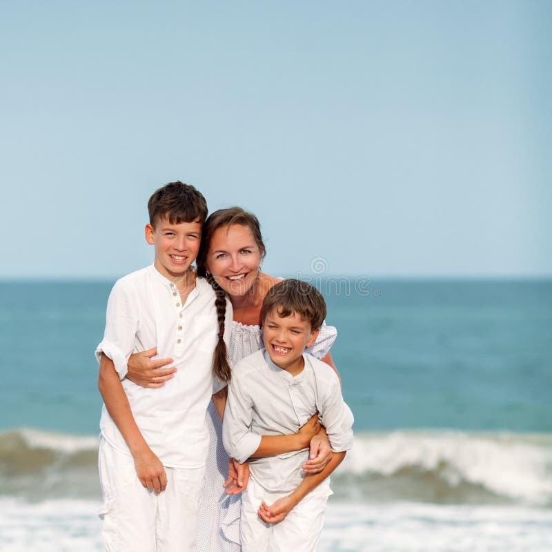 Stående av en gladlynt lycklig moder och söner på stranden royaltyfri fotografi