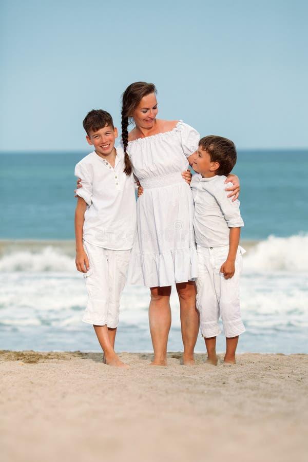 Stående av en gladlynt lycklig moder och söner på stranden arkivbild
