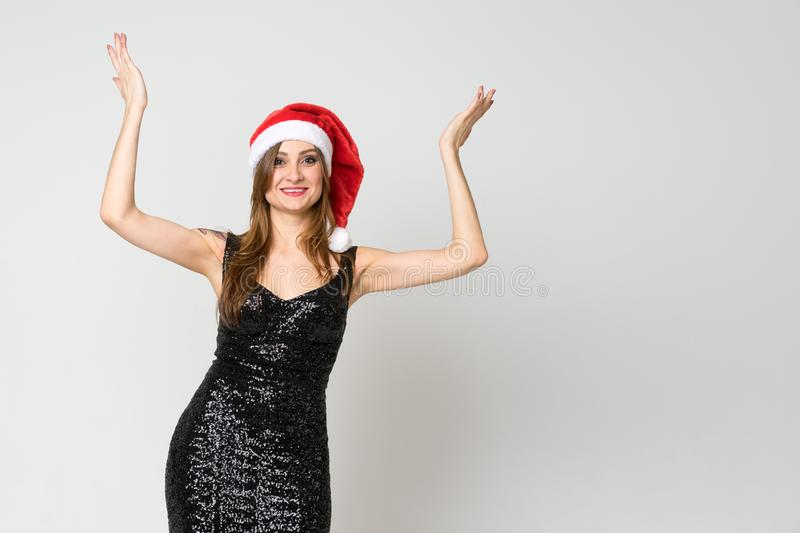 St?ende av en gladlynt skratta kvinna i julhatt och uts?kt svart kl?nning, medan st?ende h?nder lyftte och se kameran royaltyfri fotografi