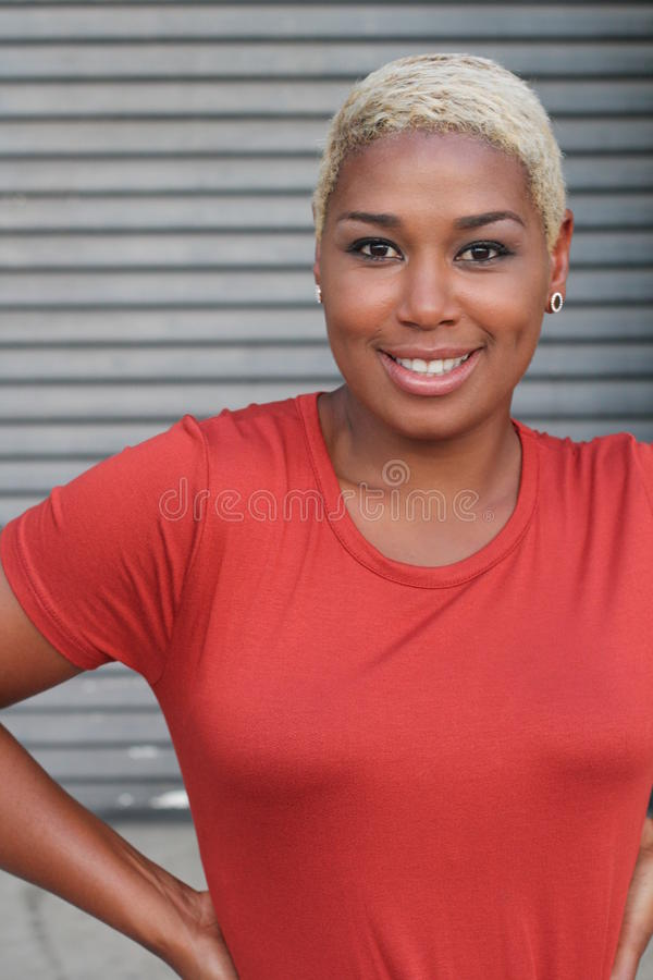 Stående av en gladlynt ung afrikansk kvinna med kort färgat blont le för frisyr fotografering för bildbyråer