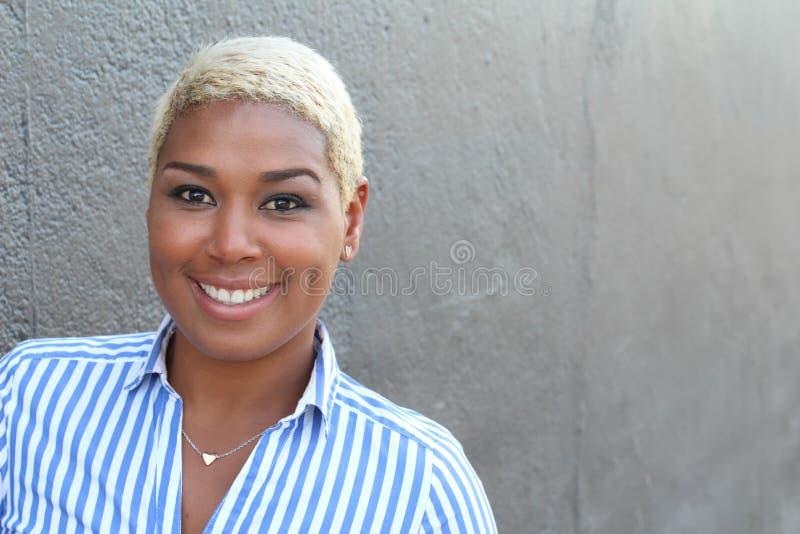 Stående av en gladlynt ung afrikansk kvinna som ler med kopieringsutrymme arkivfoton