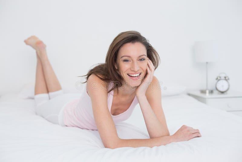 Stående av en gladlynt ung kvinna som vilar i säng royaltyfri bild