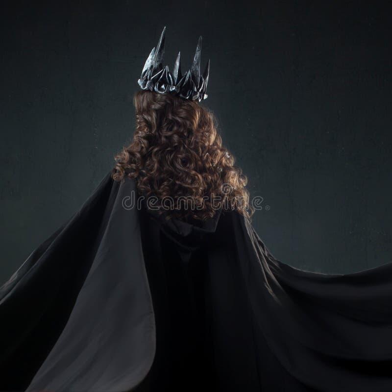 Stående av en gotisk prinsessa Härlig ung brunettkvinna i metallkrona och svart kappa arkivfoton