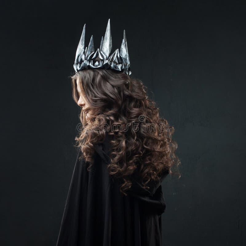 Stående av en gotisk prinsessa Härlig ung brunettkvinna i metallkrona och svart kappa fotografering för bildbyråer