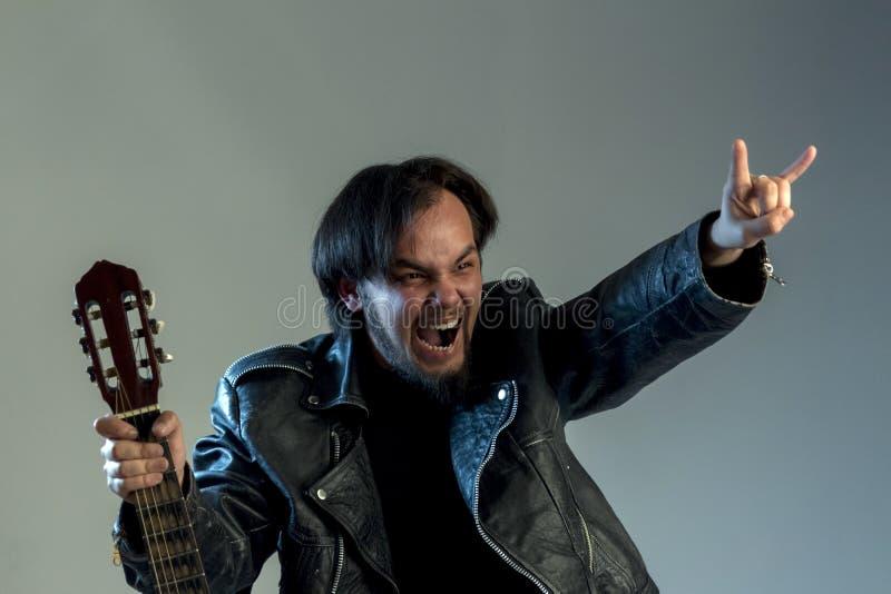 Stående av en grabb i svartkläder med ett skägg och långt hår med en gitarr En fan eller en musiker av heavy metal eller vaggar-n royaltyfria foton