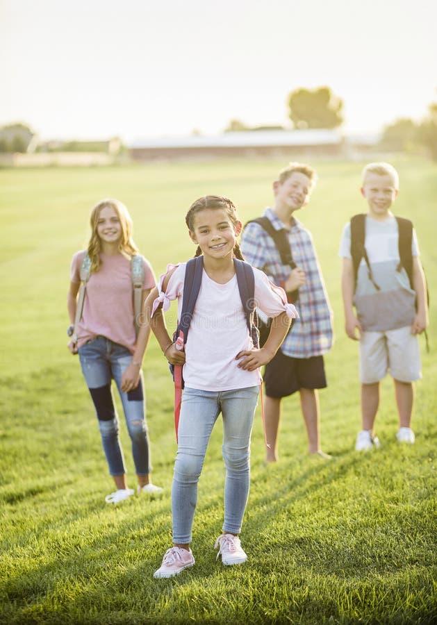Stående av en grupp av att le grundskolastudenter med ryggsäckar royaltyfria bilder