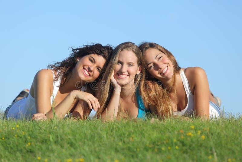 Stående av en grupp av tre lyckliga tonåringflickor som ler att ligga på gräset royaltyfria bilder
