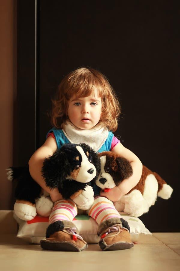 Stående av en gullig en årig flicka som hemma sitter på en kudde på golvet och kramar hennes favorit- leksaker - hundkapplöpning arkivbilder