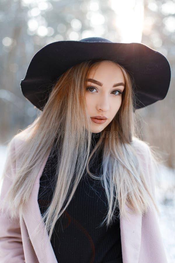 Stående av en gullig attraktiv ung kvinna med bruna ögon med kanter med blont hår i en elegant svart hatt arkivbilder