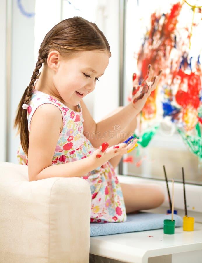 Stående av en gullig flicka som spelar med målarfärger royaltyfri foto