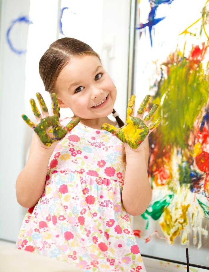 Stående av en gullig flicka som spelar med målarfärger royaltyfria foton