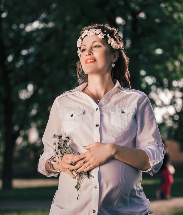 Stående av en gullig gravid kvinna med en bukett av tusenskönor fotografering för bildbyråer
