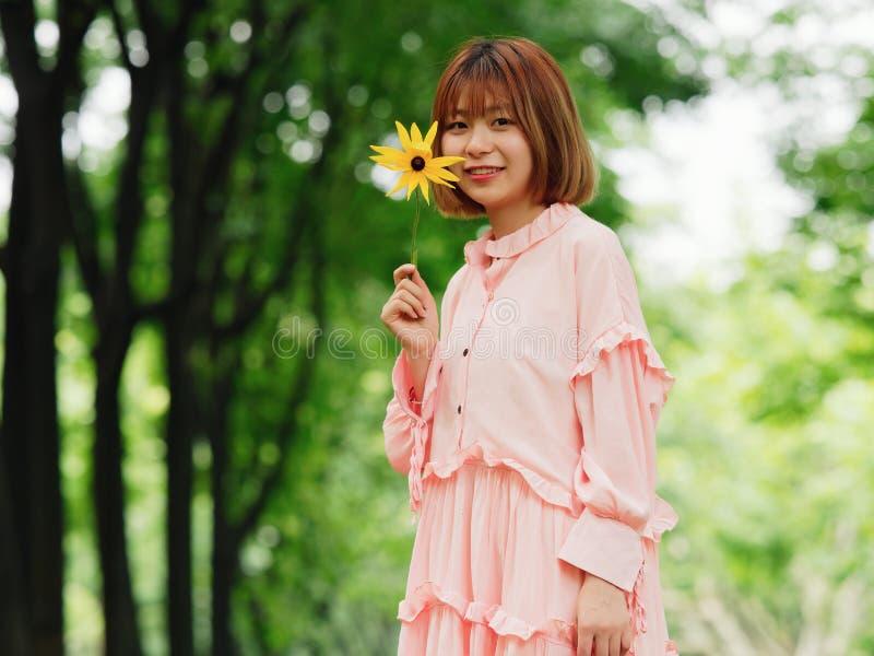 Stående av en gullig kinesisk flicka i den rosa klänningen som rymmer den lösa blomman och ler på kameran i stående för mode för  royaltyfri foto