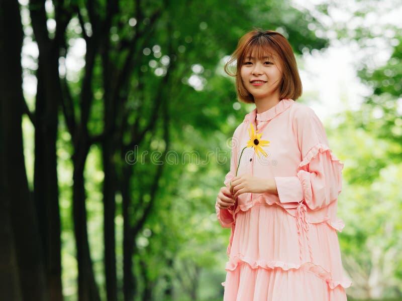 Stående av en gullig kinesisk flicka i den rosa klänningen som rymmer den lösa blomman och ler på kameran i stående för mode för  royaltyfri fotografi