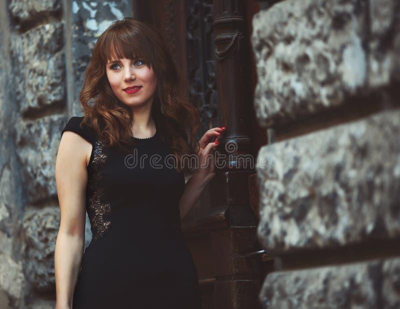 Stående av en gullig kvinna i varm klänningbenägenhet på väggen royaltyfri bild