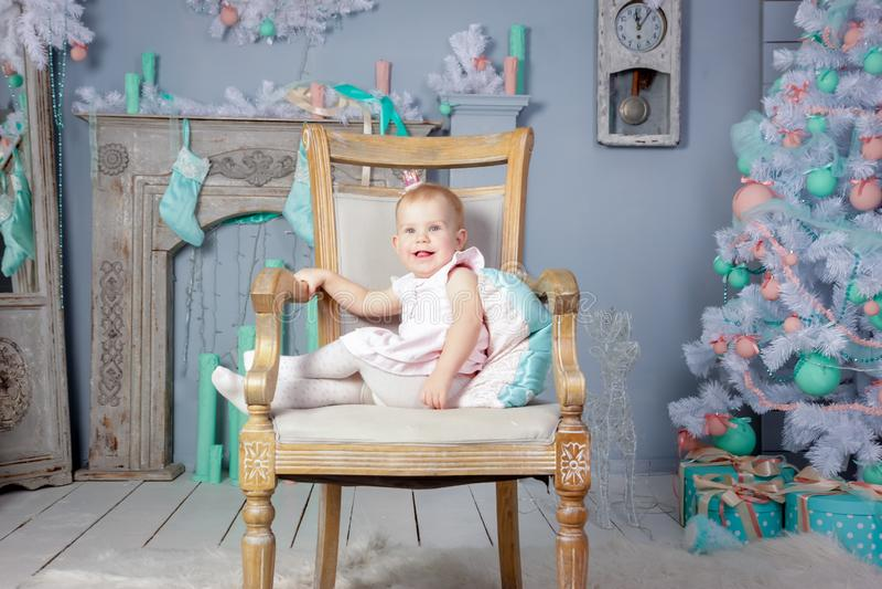 Stående av en gullig liten europeisk blond prinsessaflicka med en krona i en härlig klänning som sitter på en tappningstol i en s royaltyfri bild