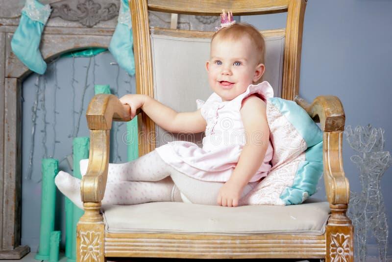 Stående av en gullig liten europeisk blond prinsessaflicka med en krona i en härlig klänning som sitter på en tappningstol i en s fotografering för bildbyråer