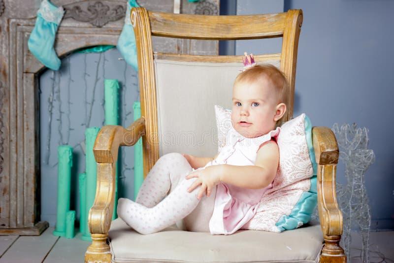 Stående av en gullig liten europeisk blond prinsessaflicka med en krona i en härlig klänning som sitter på en tappningstol i en s arkivbilder