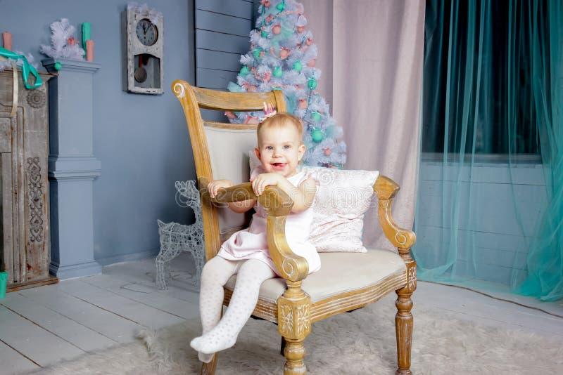Stående av en gullig liten europeisk blond prinsessaflicka med en krona i en härlig klänning som sitter på en tappningstol i en s royaltyfri fotografi
