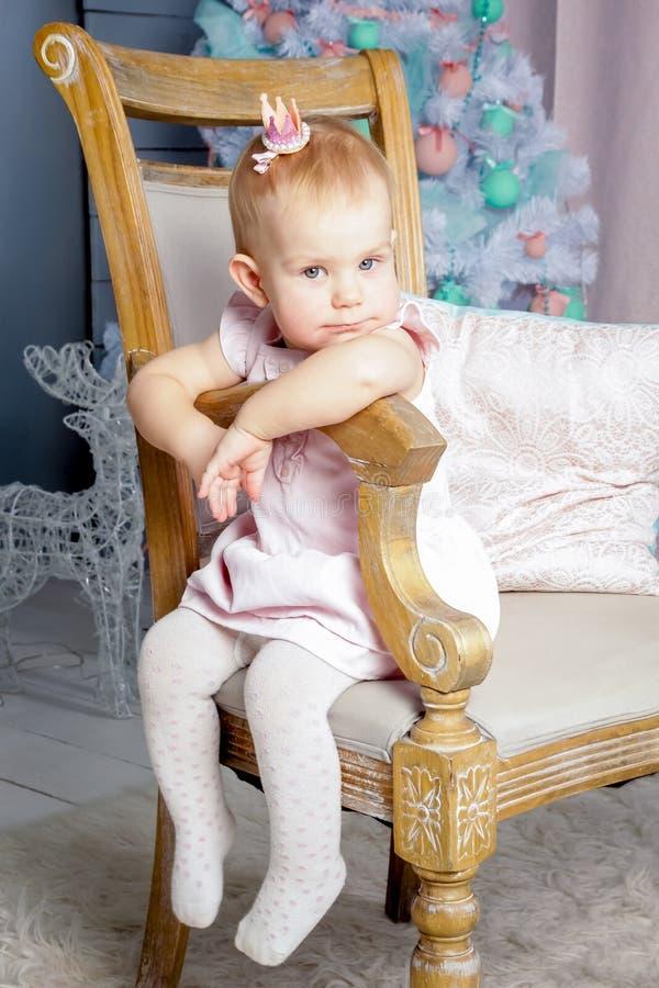Stående av en gullig liten europeisk blond prinsessaflicka med en krona i en härlig klänning som sitter på en tappningstol i en s royaltyfri foto