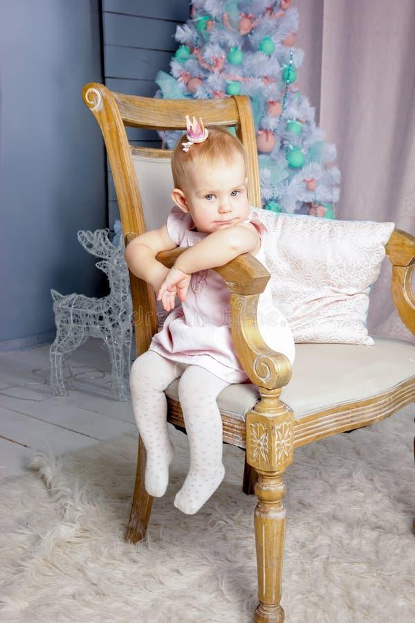 Stående av en gullig liten europeisk blond prinsessaflicka med en krona i en härlig klänning som sitter på en tappningstol i en s arkivbild
