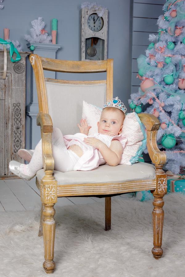 Stående av en gullig liten europeisk blond prinsessaflicka med en krona i en härlig klänning som sitter på en tappningstol i en s arkivfoton