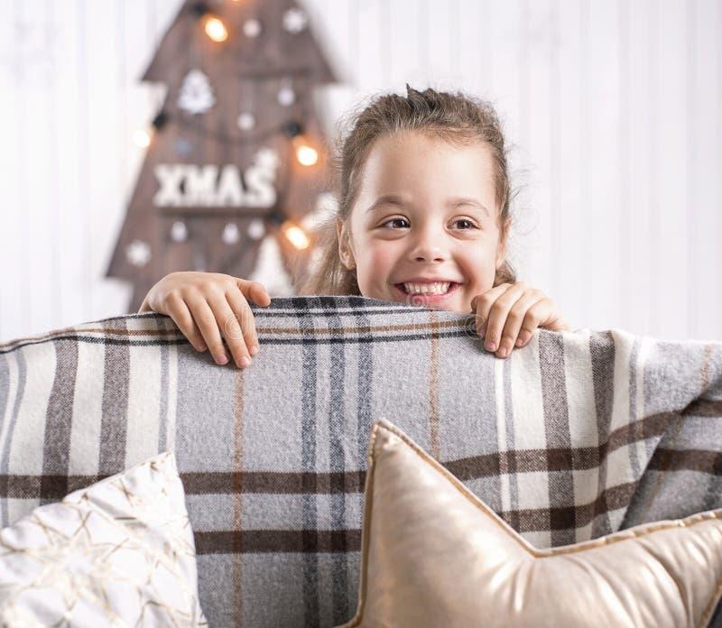 Stående av en gullig liten flicka i en modern inre arkivbild