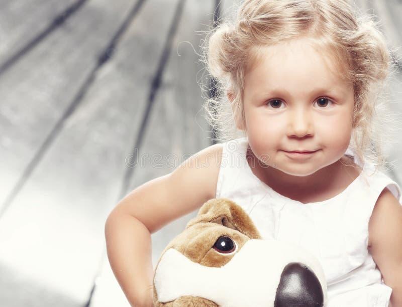 Stående av en gullig liten flicka i sammanträde för tillfällig klänning med en flott leksak i studio arkivbild