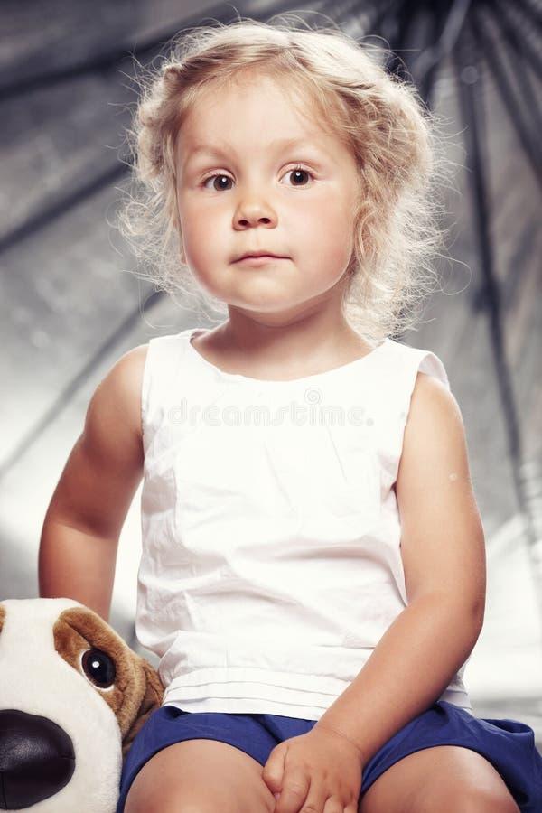 Stående av en gullig liten flicka i sammanträde för tillfällig klänning med en flott leksak i studio royaltyfri foto