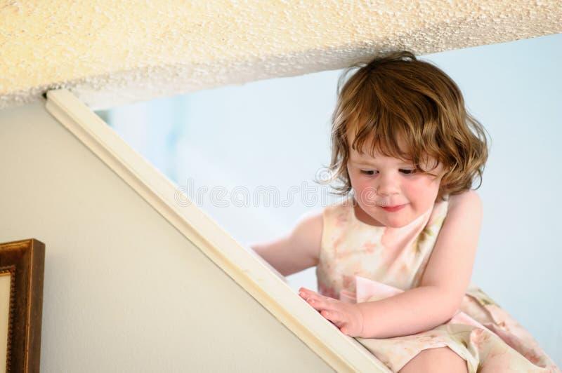 Stående av en gullig liten flicka inom på trappa royaltyfria bilder