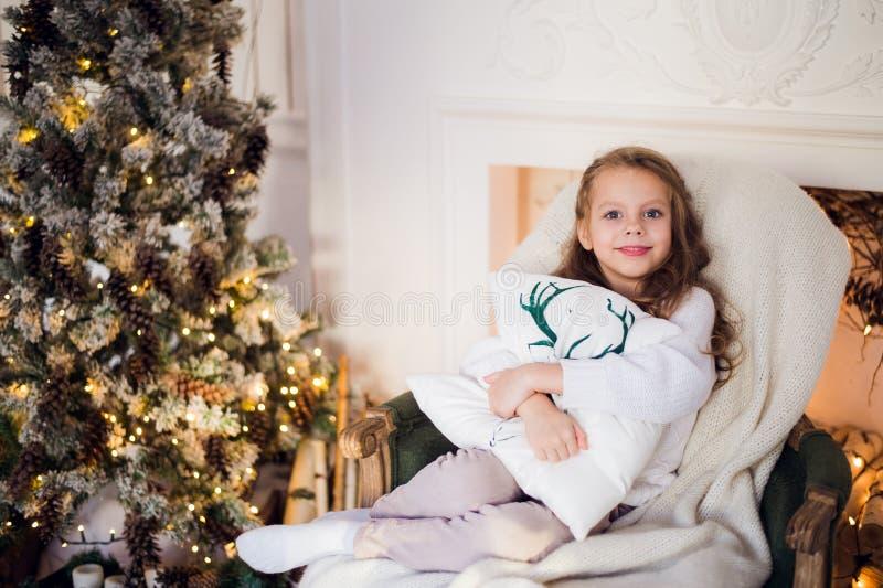 Stående av en gullig liten flicka som hemma omfamnar kudden mot julträd royaltyfria foton