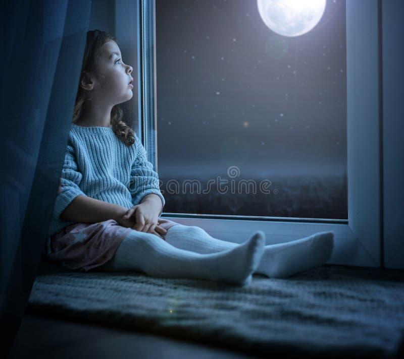 Stående av en gullig liten flicka som ser nattmånen arkivbilder